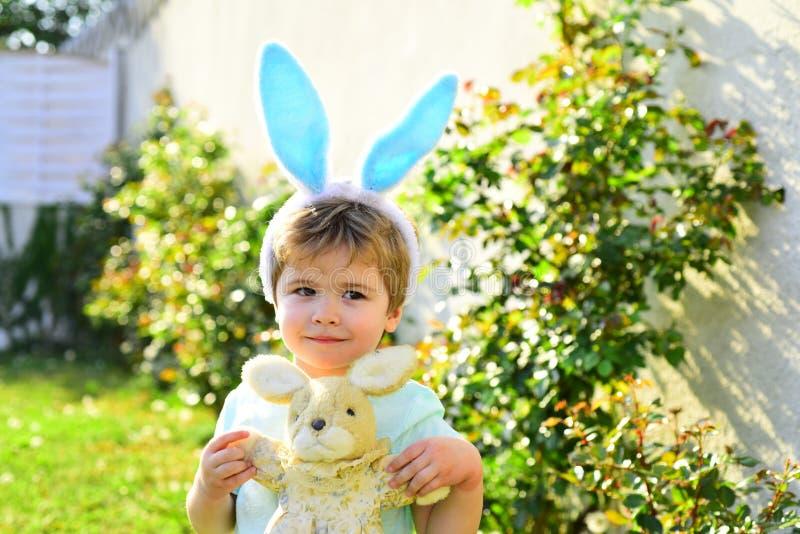 o r 逗人喜爱的兔宝宝 儿童男孩佩带的兔宝宝耳朵 r 幸福家庭和 免版税库存图片