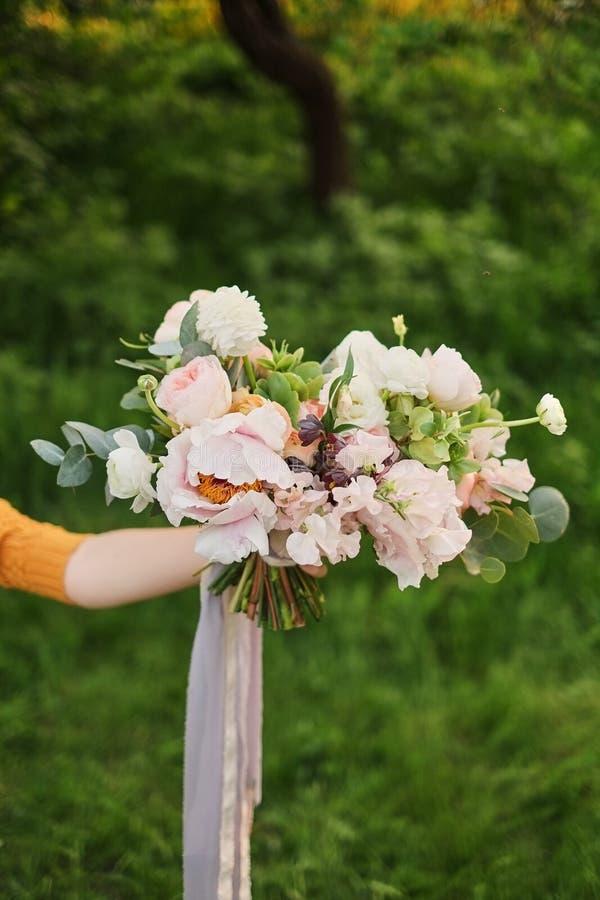 O ramalhete da noiva A mulher da flor realiza em sua mão um ramalhete bonito do casamento das flores para a noiva fotografia de stock royalty free