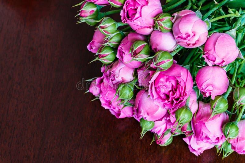 O ramalhete das peônias cor-de-rosa bonitas, rosas com folhas verdes encontra-se em uma tabela de madeira imagem de stock