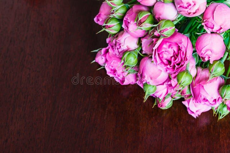 O ramalhete das peônias cor-de-rosa bonitas, rosas com folhas verdes encontra-se em uma tabela de madeira imagem de stock royalty free