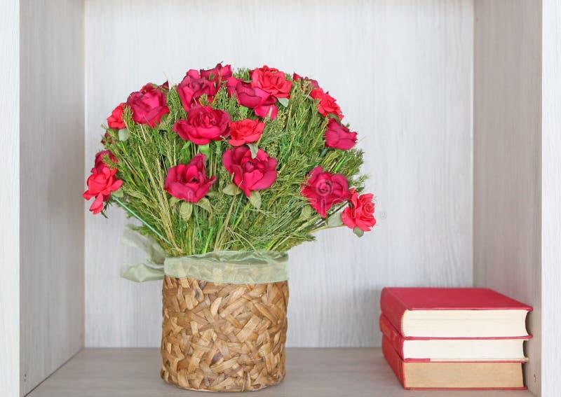O ramalhete de rosas vermelhas artificiais recicla dentro o vaso e os livros fotos de stock