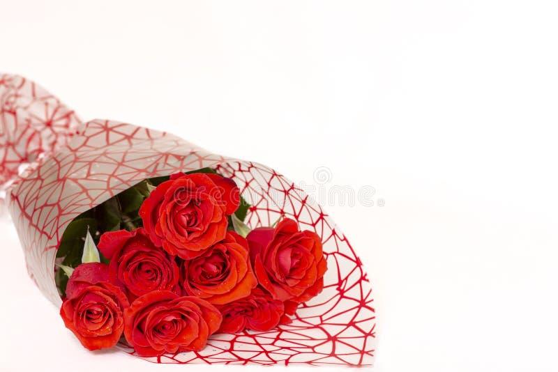 O ramalhete de rosas vermelhas encontra-se em um fundo branco imagens de stock royalty free