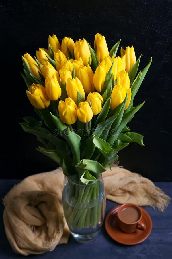 O ramalhete de tulipas da mola floresce no vaso no fundo preto Tulipas amarelas fotos de stock royalty free