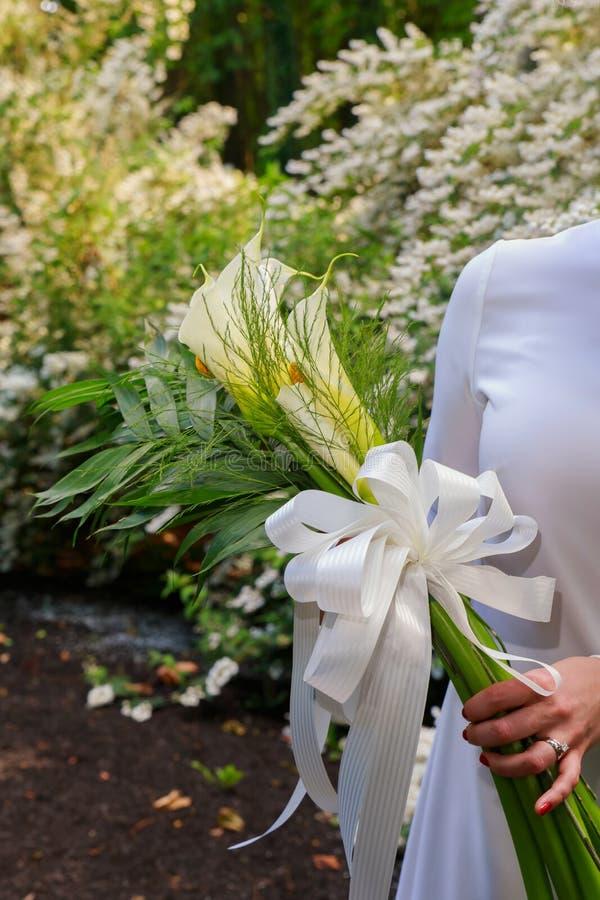O ramalhete do casamento com kala floresce o bride& x27; mão de s fora imagens de stock