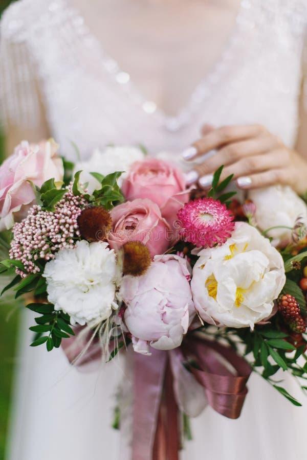 O ramalhete do casamento com a rosa do branco e do rosa, as peônias e as hortaliças que estão nas mãos da noiva no laço branco ve fotografia de stock