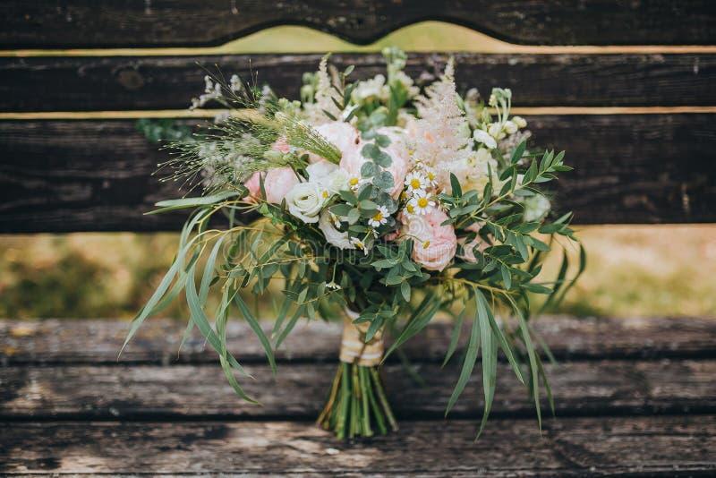 O ramalhete do casamento das flores e das hortaliças está em um banco de madeira velho fotos de stock