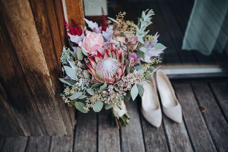 O ramalhete do casamento das flores e dos verdes com fita está em um assoalho de madeira ao lado das sapatas do ` s da noiva foto de stock royalty free