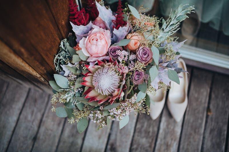 O ramalhete do casamento das flores e dos verdes com fita está em um assoalho de madeira ao lado das sapatas do ` s da noiva foto de stock