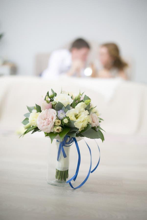 O ramalhete do casamento das rosas com uma fita azul custa em um vaso Na perspectiva dos recém-casados encontre-se em uma cama imagens de stock