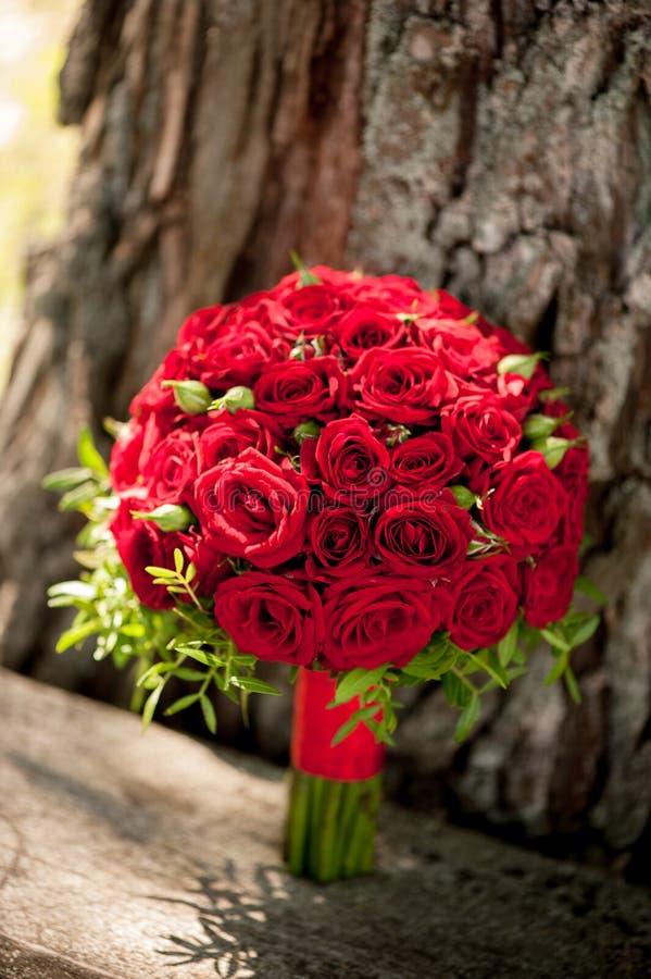 O ramalhete do casamento de rosas vermelhas est? no fundo da casca de ?rvore foto de stock royalty free