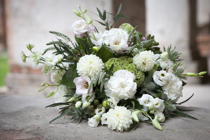 O ramalhete do casamento nos tons brancos do lisianthus, das rosas, das dálias e do eucalipto encontrando-se no pavimento antigo  fotografia de stock