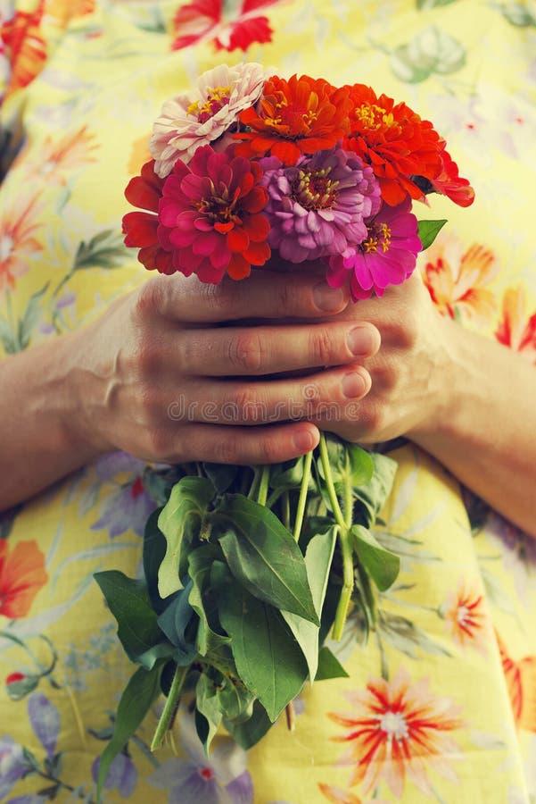 O ramalhete do verão brilhante floresce nas mãos da menina em um vestido amarelo fotos de stock royalty free