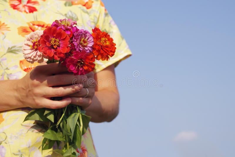O ramalhete do verão brilhante floresce nas mãos da menina em um vestido amarelo contra o céu azul imagem de stock royalty free