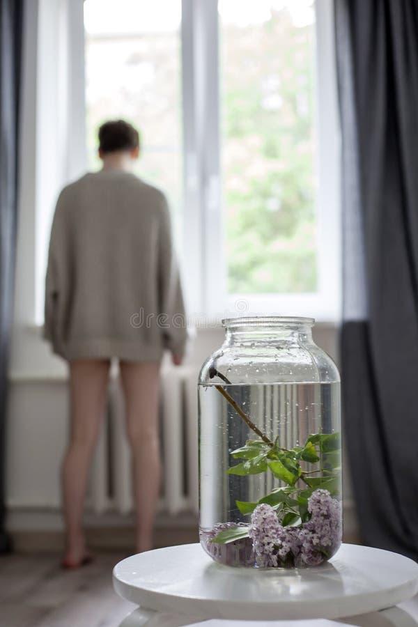 O ramalhete dos galhos lil?s em um frasco verde transparente na cadeira branca como uma decora??o do interior fotografia de stock