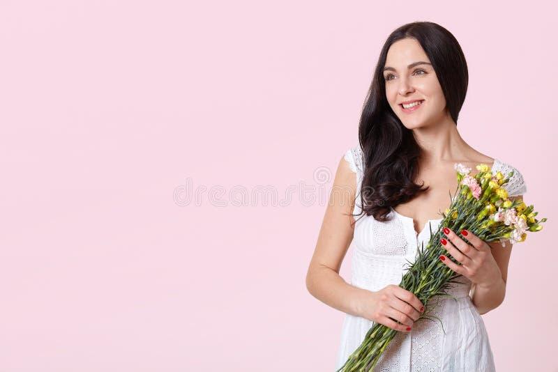O ramalhete feliz novo da terra arrendada da mulher, olha pensativamente de lado, sonhando sobre seu fã misterioso, vestido branc fotos de stock