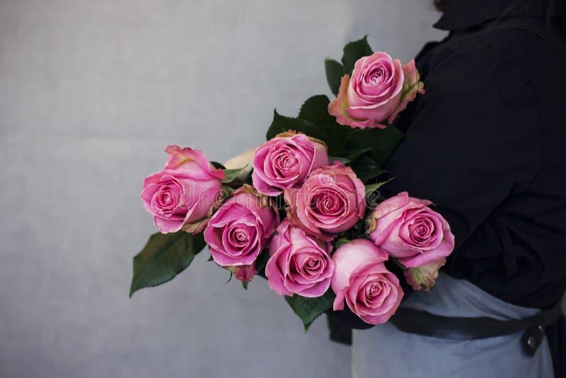 O ramalhete grande de rosas cor-de-rosa bonitas nas mãos da mulher fotos de stock