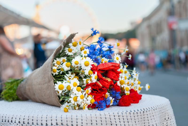 O ramalhete grande dos wildflowers (camomila, knapweed, papoila) coloca na tabela com toalha de mesa branca dos azuis celestes no imagem de stock royalty free