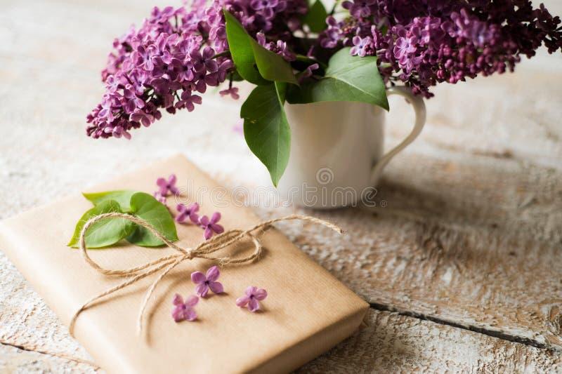 O ramalhete lilás roxo no vaso e no presente colocou na tabela de madeira fotografia de stock