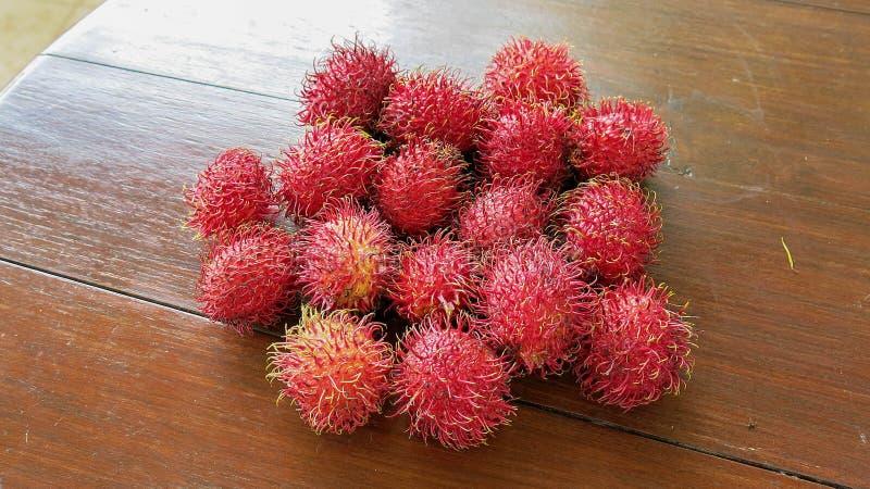 O Rambutan ? um fruto tropical doce Fruto maduro vermelho do rambutan na tabela de madeira Fruto fresco completo do néctar doce foto de stock royalty free