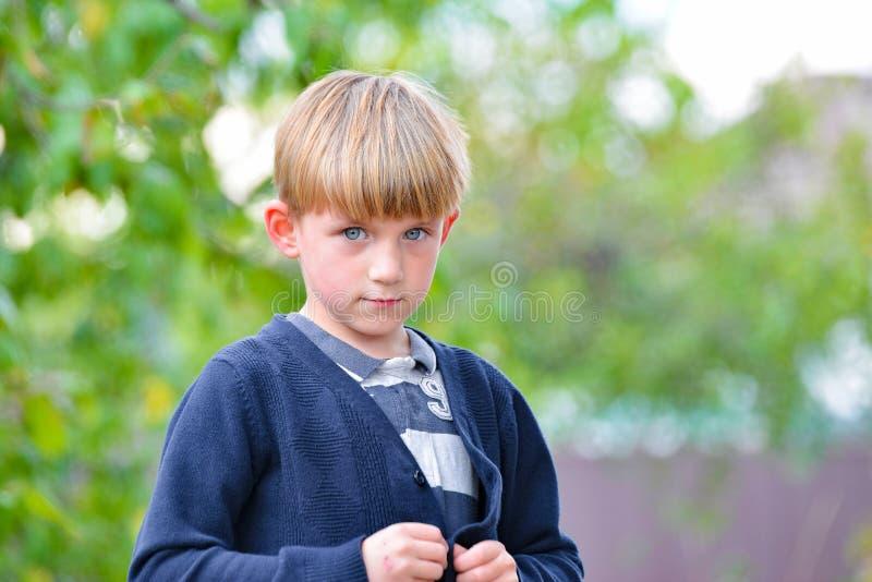 O rapaz delinquente foi punido e olha à porta fechada com tristeza nos olhos imagens de stock