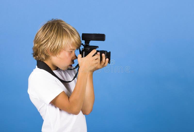 O rapaz pequeno é um fotógrafo imagens de stock royalty free
