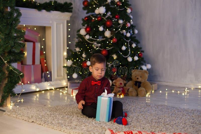 O rapaz pequeno abre presentes em luzes do feriado do ano novo do Natal fotografia de stock royalty free