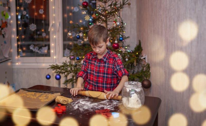 O rapaz pequeno adorável está preparando o pão-de-espécie, coze cookies na cozinha do Natal imagem de stock royalty free