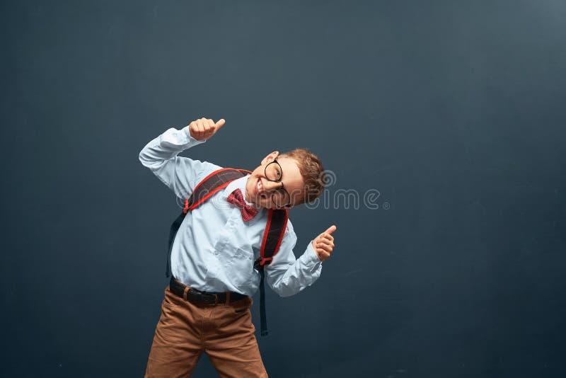 O rapaz pequeno alegre, em um fundo preto com uma pasta atrás de seus ombros mostra um gesto da vitória, alegria do sucesso feliz fotos de stock royalty free