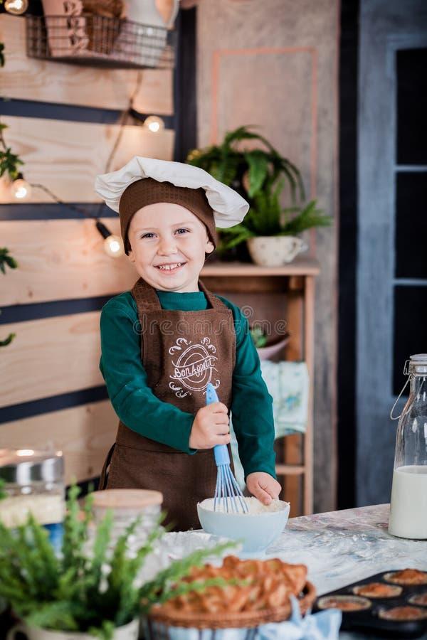 O rapaz pequeno alegre está cozendo bolos Padeiro pequeno Bolos franceses f imagem de stock
