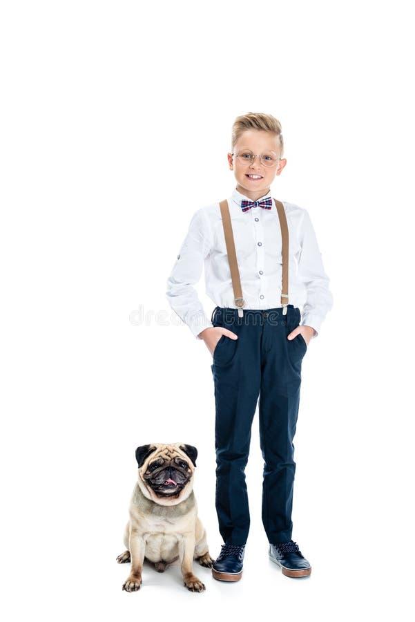 o rapaz pequeno alegre nos monóculos que estão com mãos em uns bolsos aproxima o cão fotos de stock