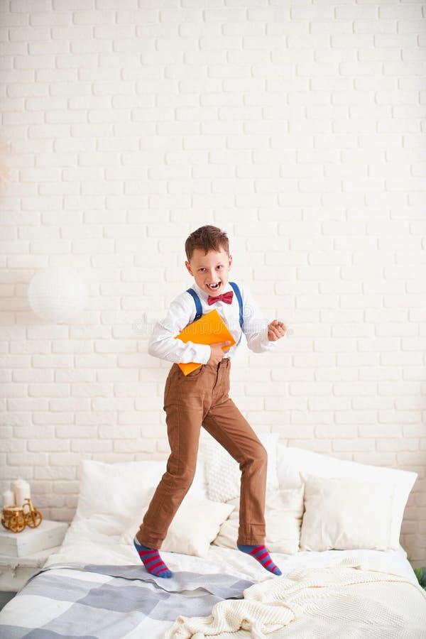 O rapaz pequeno alegre salta na cama com um globo em suas mãos e aprecia o começo do ano escolar a criança feliz é aproximadament fotos de stock
