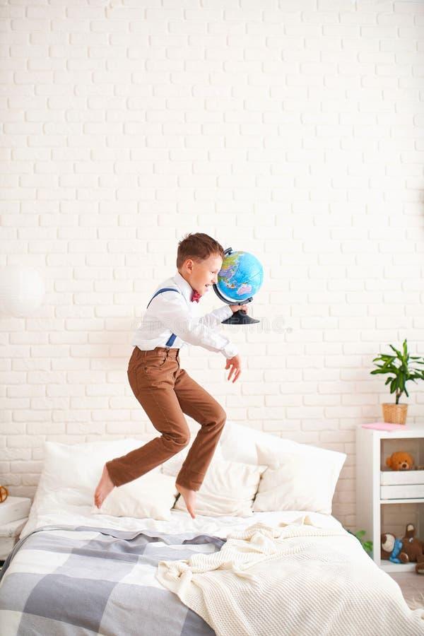O rapaz pequeno alegre salta na cama com um globo em suas mãos e aprecia o começo do ano escolar a criança feliz é aproximadament imagens de stock