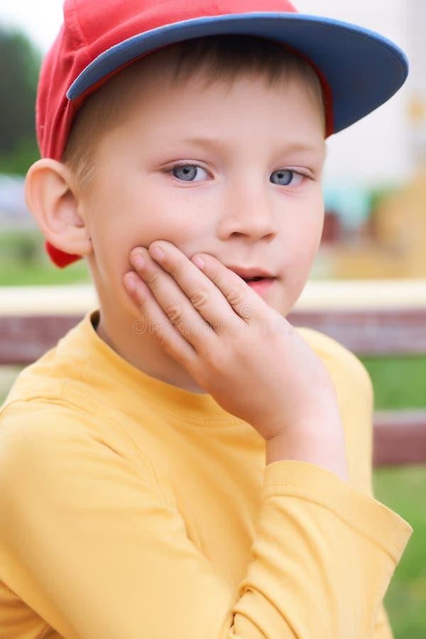 O rapaz pequeno ao estilo do hip-hop O menino olha a câmera com sua mão que sustenta seu mordente imagem de stock royalty free