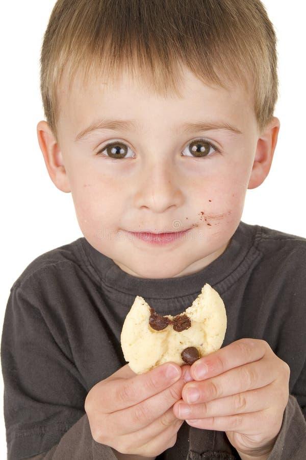 O rapaz pequeno aprecia comer o bolinho fotografia de stock