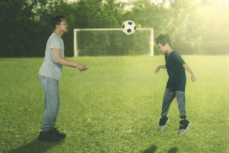O rapaz pequeno aprende a dirigir uma bola com seu pai imagens de stock
