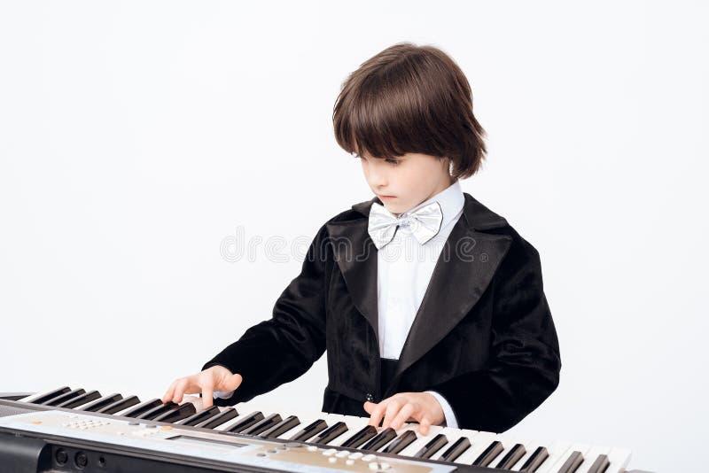 O rapaz pequeno aprende o jogo no sintetizador O menino de cabelo escuro nos teclados dos jogos do terno imagens de stock