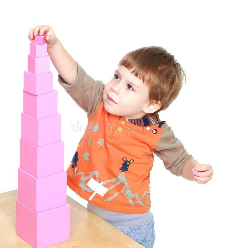 O rapaz pequeno aprende pôr a pirâmide cor-de-rosa em Montessori imagem de stock royalty free