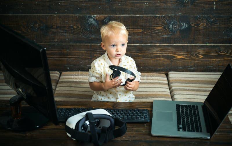 O rapaz pequeno aprende usando a informática  Desenvolvimento adiantado com nova tecnologia Digital o vosso imagem de stock