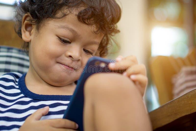 O rapaz pequeno asiático bonito está olhando o smartphone disponível foto de stock
