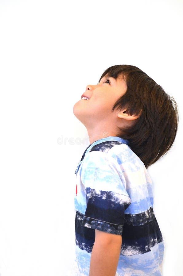 O rapaz pequeno asiático olha acima imagem de stock