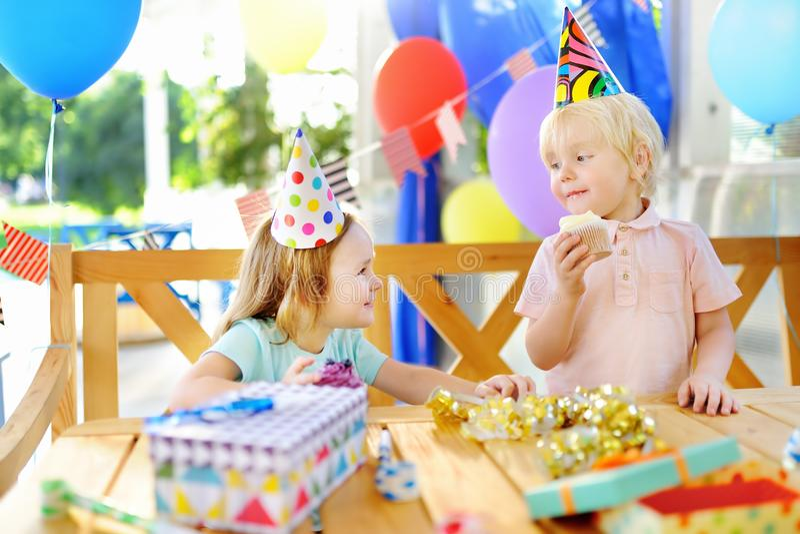 O rapaz pequeno bonito e a menina que têm o divertimento e comemoram a festa de anos com decoração colorida e endurecem fotografia de stock royalty free