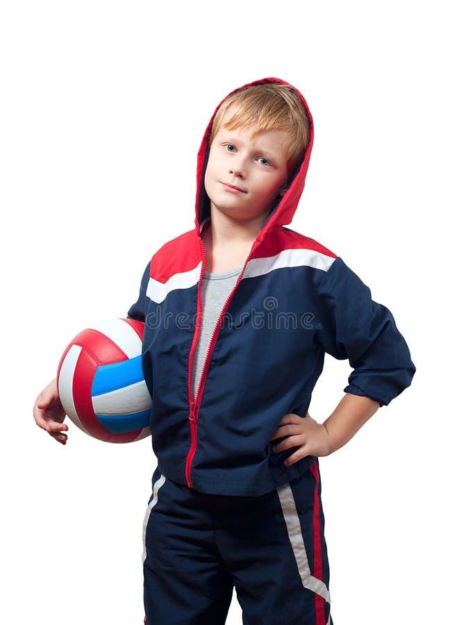 O rapaz pequeno bonito em um jumpsuit prende um voleibol imagens de stock