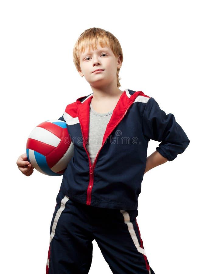 O rapaz pequeno bonito em um jumpsuit prende um volleyba fotografia de stock royalty free