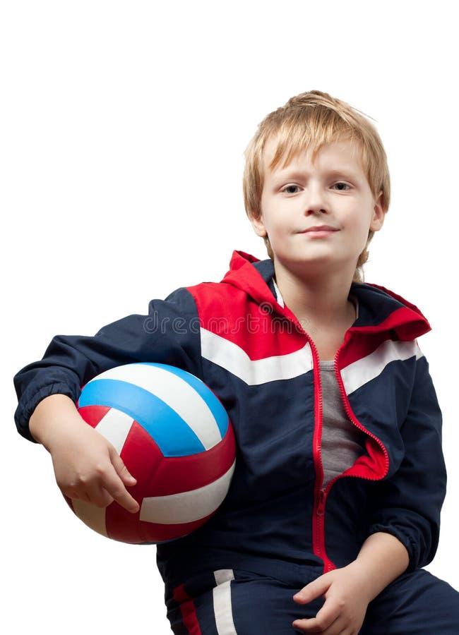 O rapaz pequeno bonito em um jumpsuit prende um volleyba imagens de stock