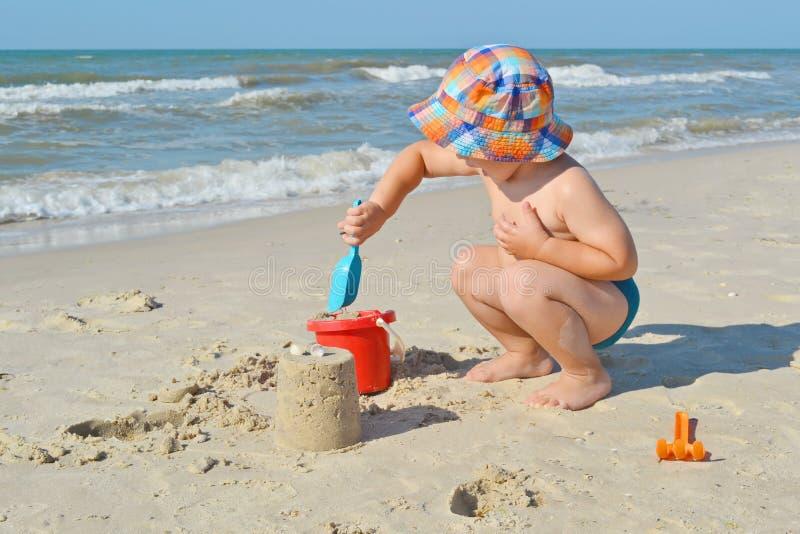 O rapaz pequeno bonito está construindo o castelo da areia no litoral foto de stock