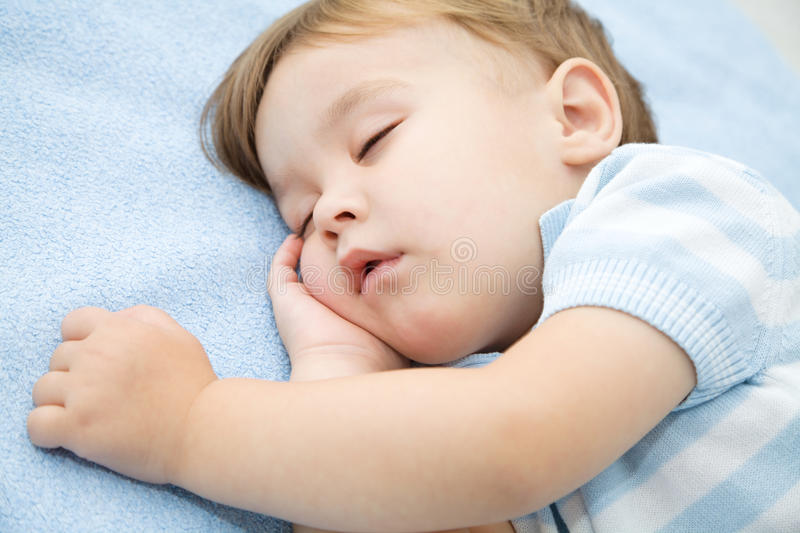 O rapaz pequeno bonito está dormindo imagem de stock royalty free