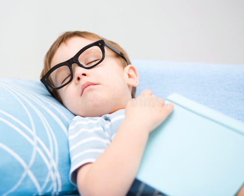 O rapaz pequeno bonito está dormindo imagem de stock
