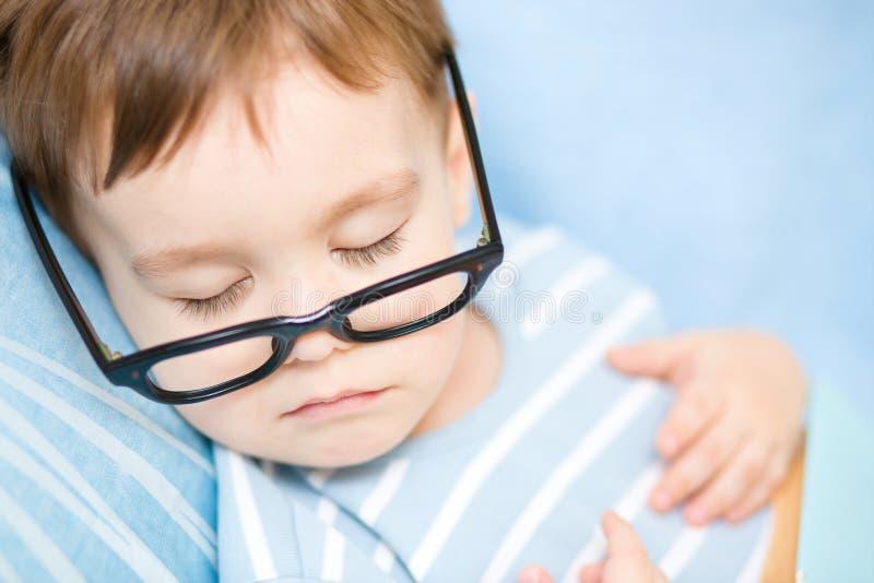 O rapaz pequeno bonito está dormindo imagens de stock royalty free