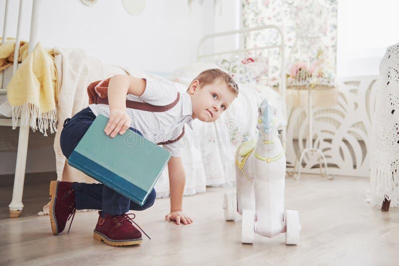 O rapaz pequeno bonito está indo educar pela primeira vez Criança com saco e livro de escola A criança faz uma pasta, sala de cri imagem de stock royalty free