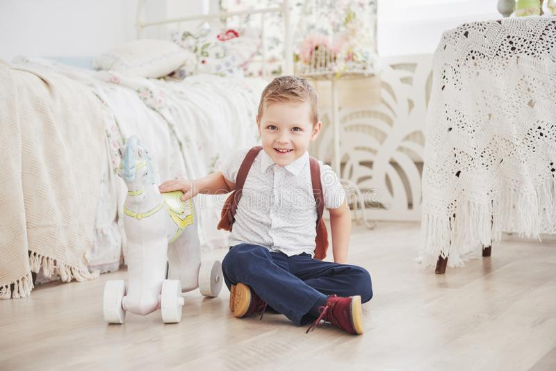 O rapaz pequeno bonito está indo educar pela primeira vez Criança com saco e livro de escola A criança faz uma pasta, sala de cri fotos de stock